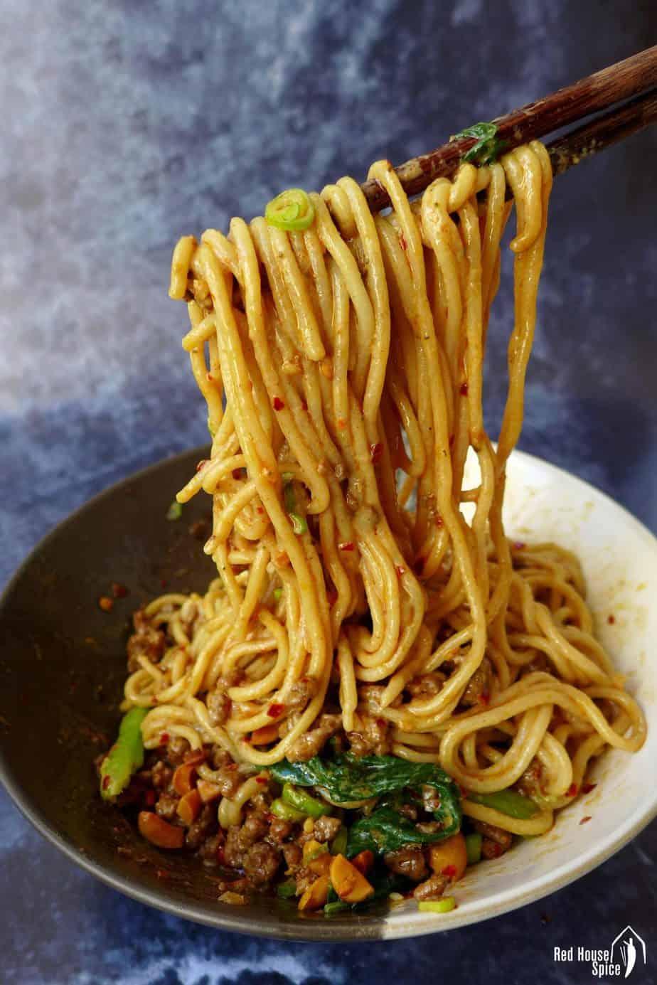 Dan Dan noodles lifted by chopsticks