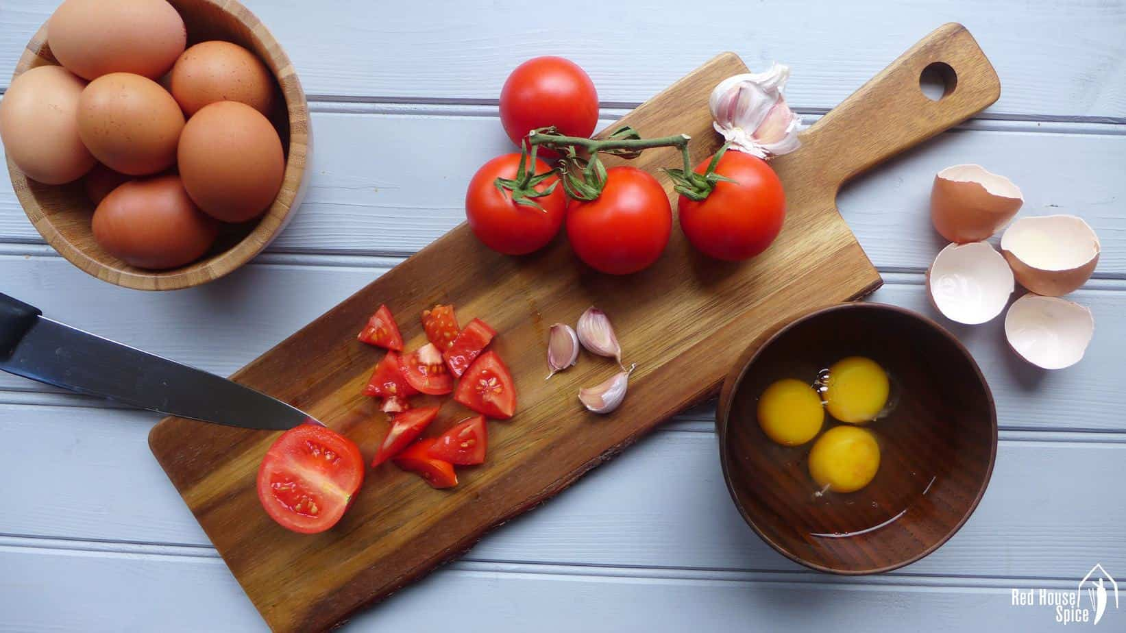 Eggs, tomato and garlic on a chopping board.