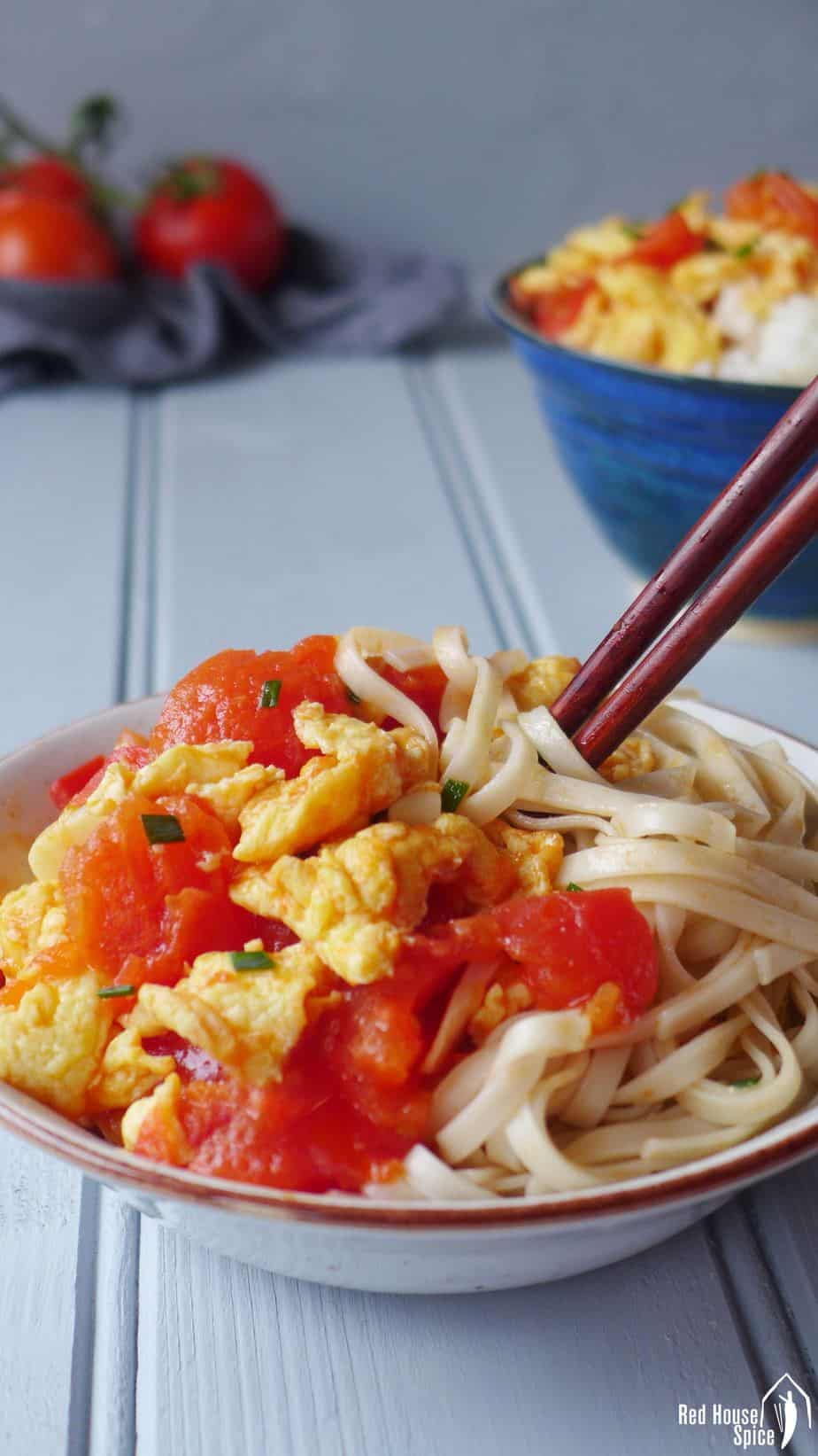 Tomato and egg stir-fry over a bowl of noodles.