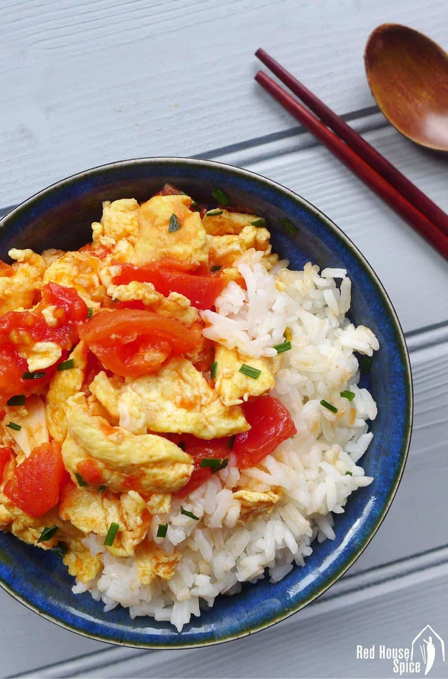Tomato and egg stir-fry over a bowl of rice
