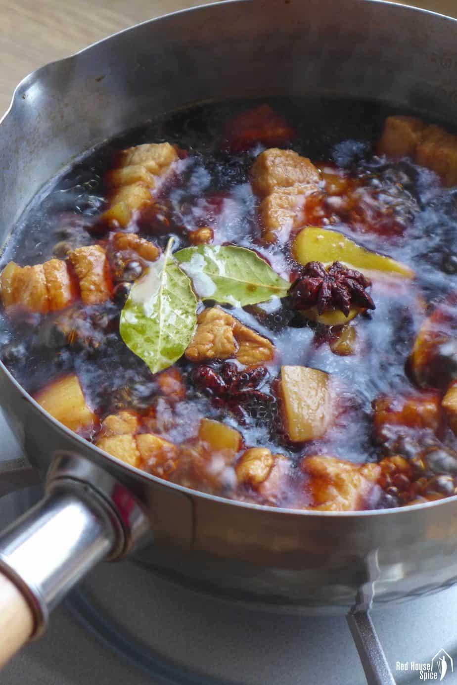 boiling pork chunks in a dark broth