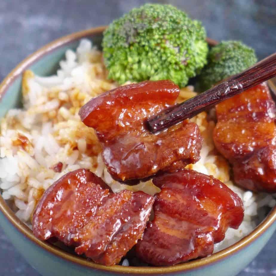 chopsticks picking up a pieces of braised pork belly
