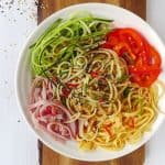 A bowl of spaghetti noodles with ham, eggs, courgette & pepper.