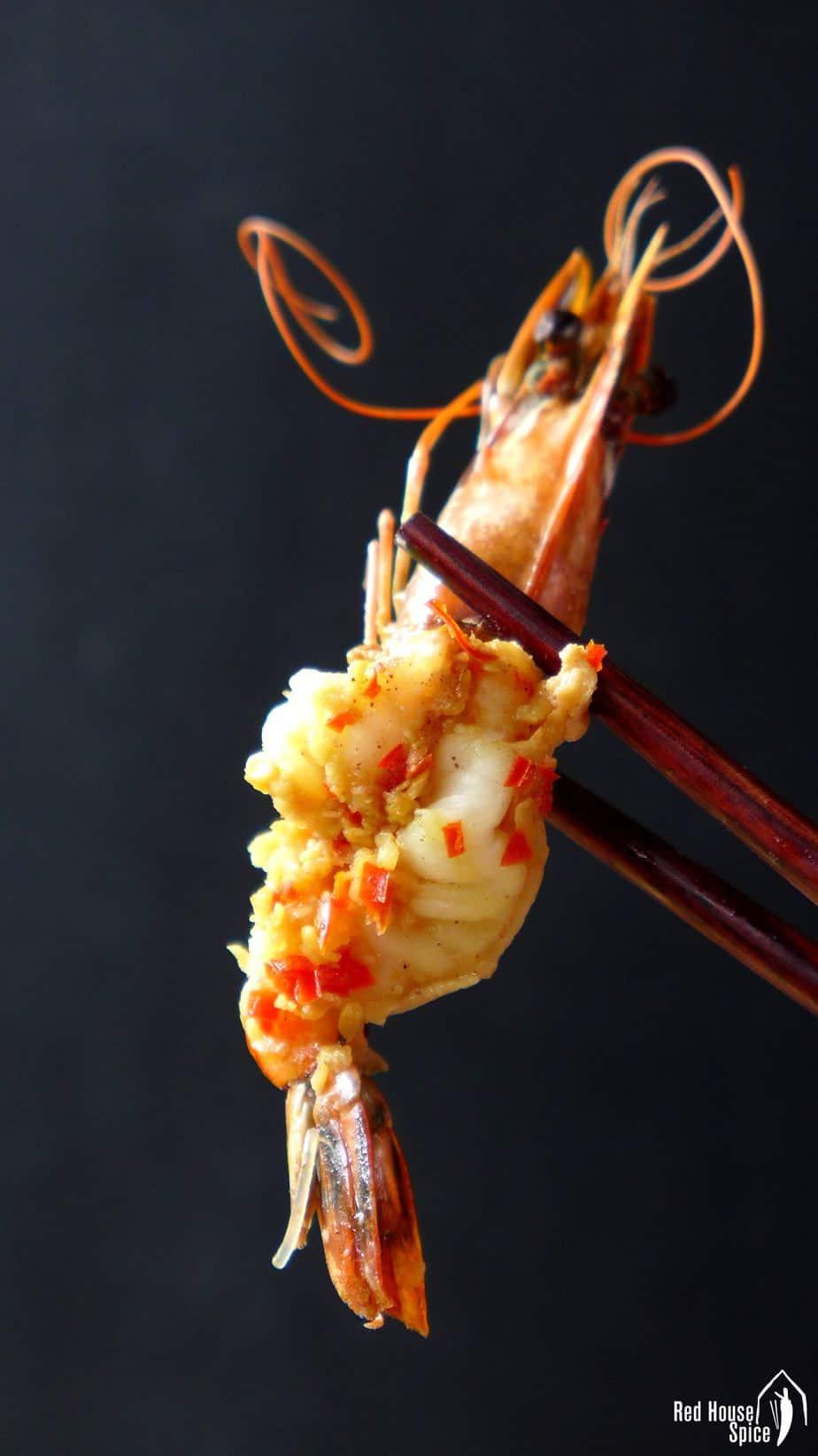 A garlic seasoned prawn held by a pair of chopsticks.