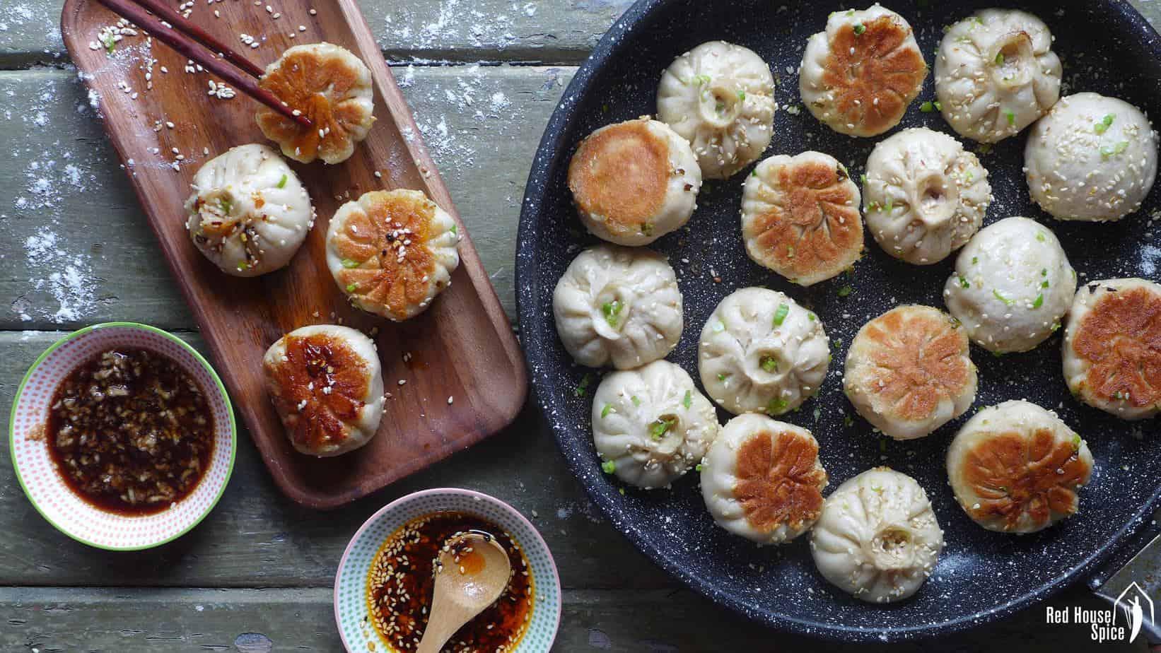 Sheng Jian Bao (pan-fried pork buns) in a plate and in a frying pan.