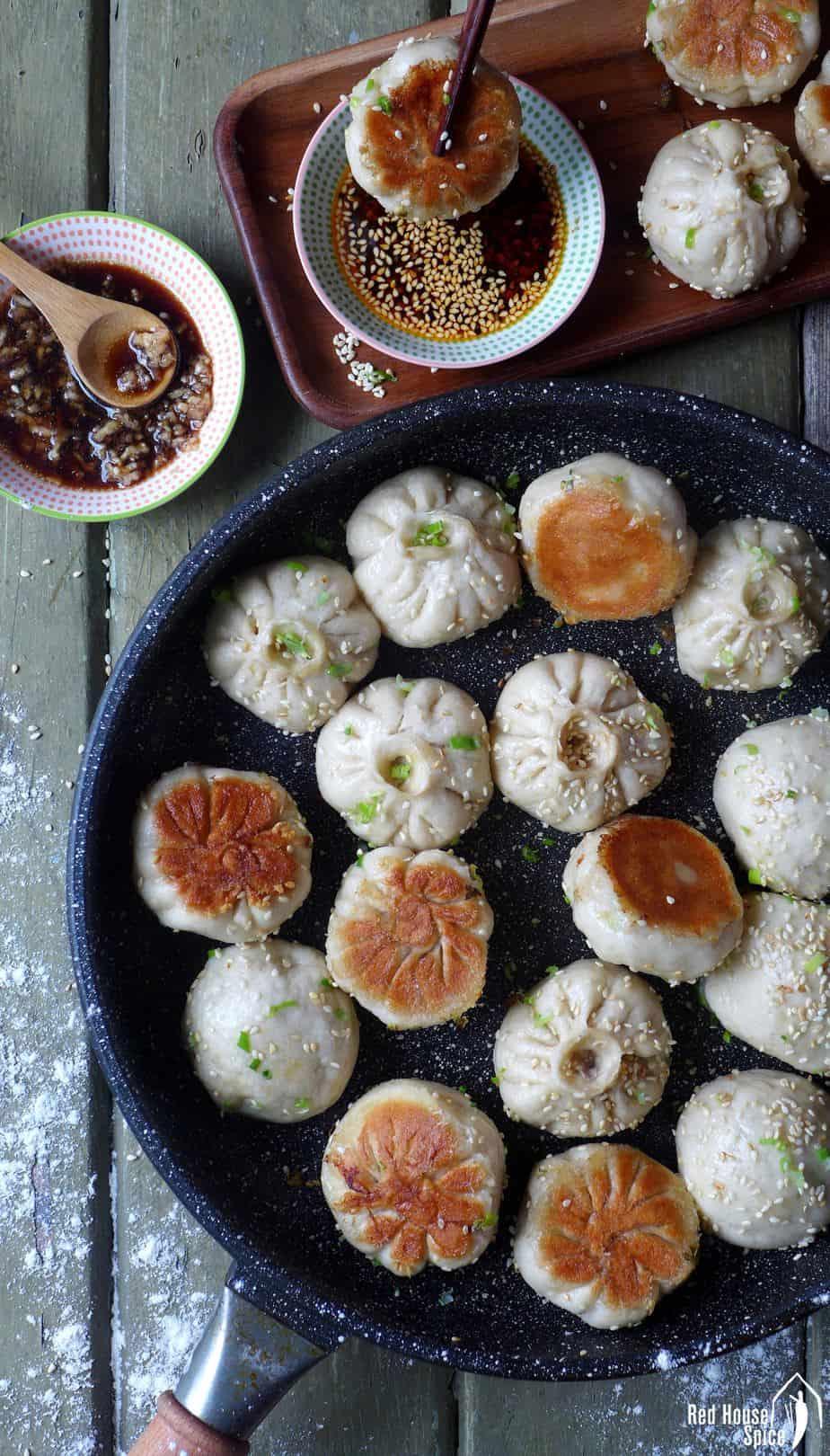Sheng Jian Bao (pan-fried pork buns) cooked in a black frying pan.
