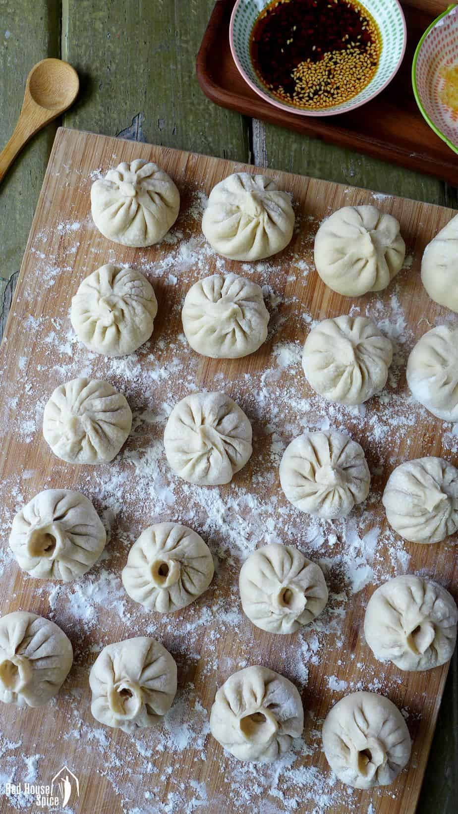 Freshly assembled Sheng Jian Bao (pan-fried pork buns) on a chopping board ready to be cooked.
