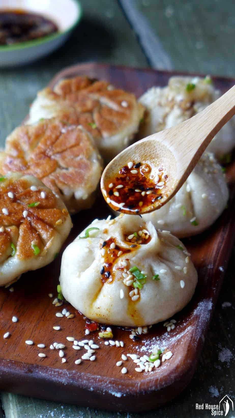 Six freshly cooked Sheng Jian Bao (生煎包, pan-fried pork buns) served with Chinese chilli oil.