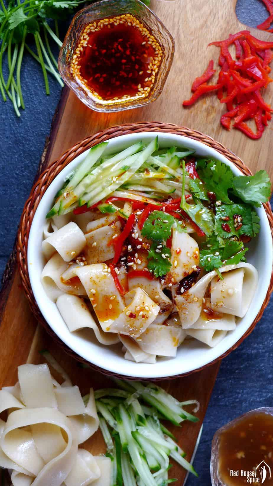 A bowl of Liang Pi, cold skin noodles with fresh chilli & chilli oil on the side.