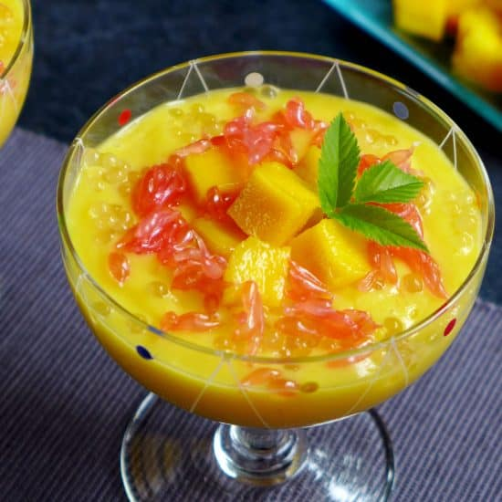A dessert glass filled with mango puree and grapefruit pieces