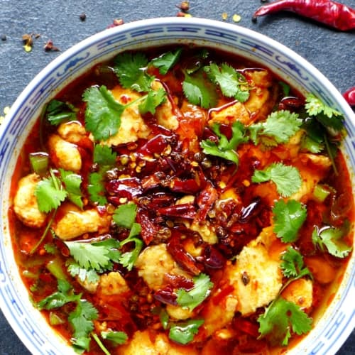 Sichuan boiled fish garnished with coriander and topped with dried chilli and Sichuan pepper.