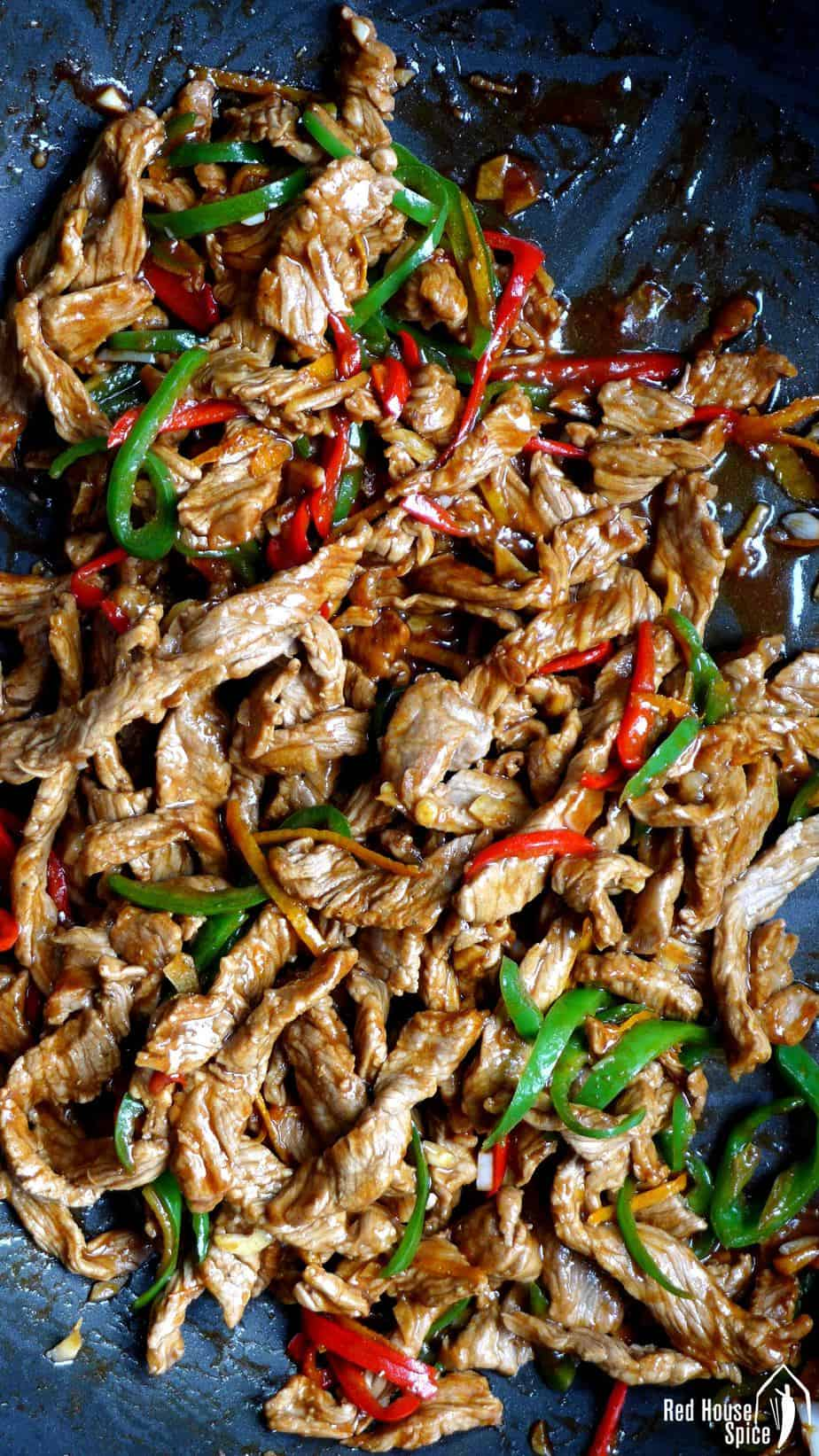 Beef strips and chillies in a wok