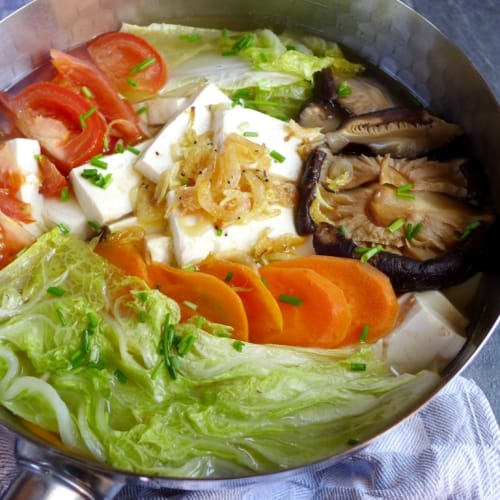 A pot of tofu soup with various vegetables