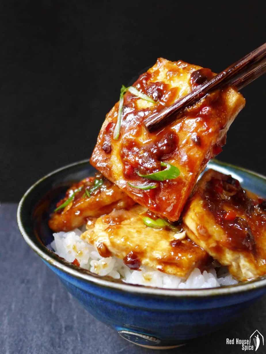 Chopsticks holding a piece of fried tofu