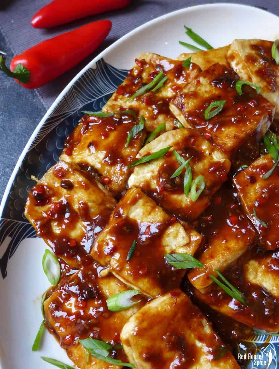 A plate of pan-fried tofu coated with garlic sauce