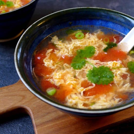 A bowl of Chinese egg drop soup with diced tomato and garnished with coriander.