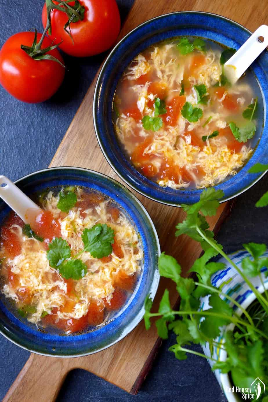 Two bowls of egg drop soup with tomatoes
