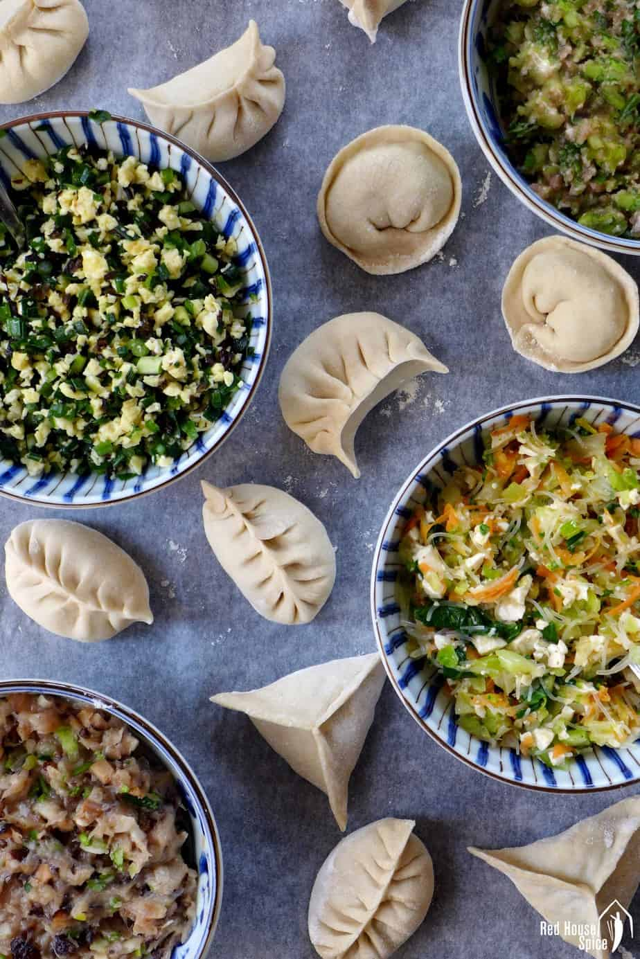 Four bowls of different dumpling fillings and some dumplings in different shape.
