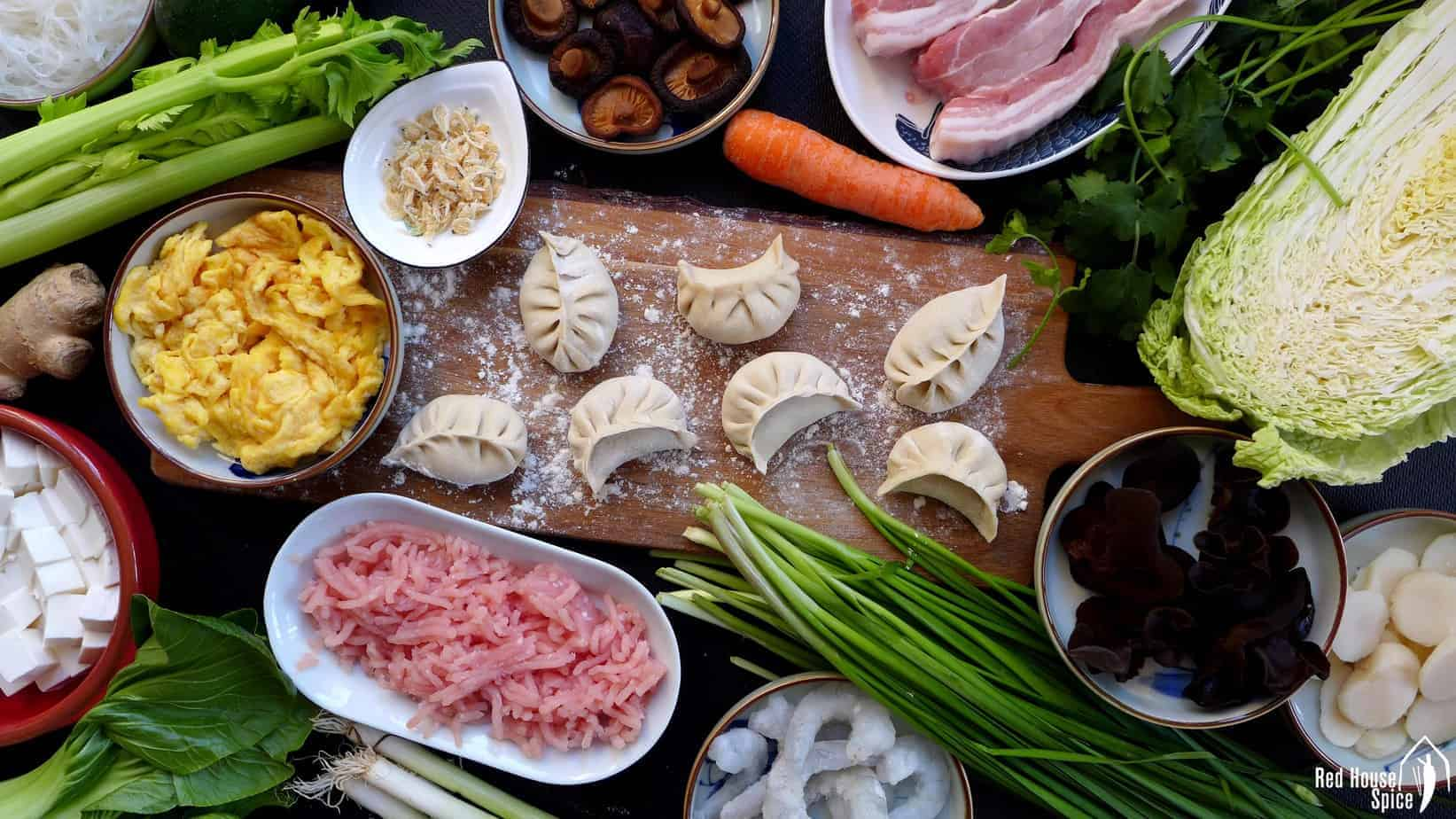 Dumplings surrounded by and raw ingredients for making dumpling fillings