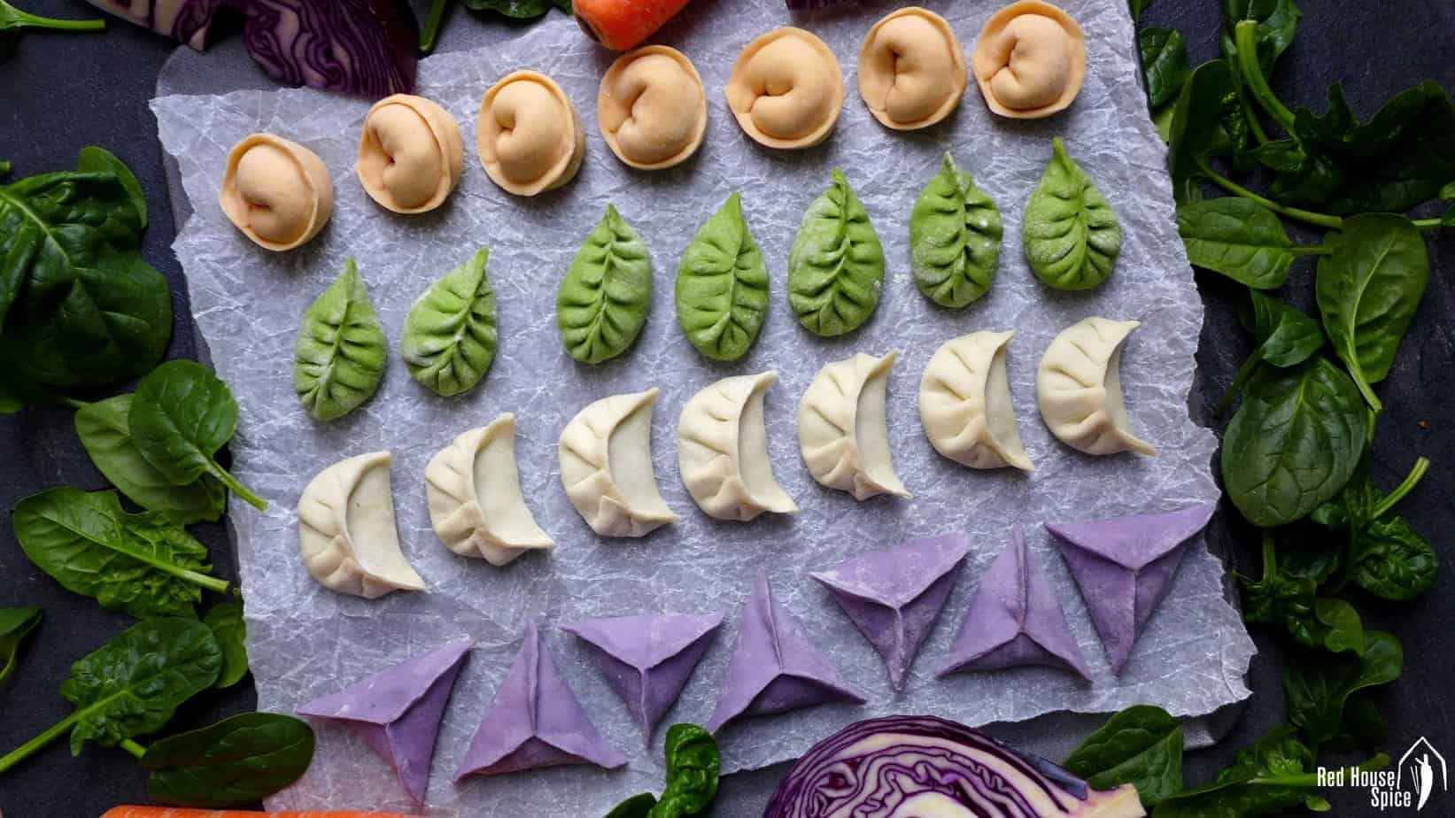 Lines of dumplings in white, green, orange and purple colour