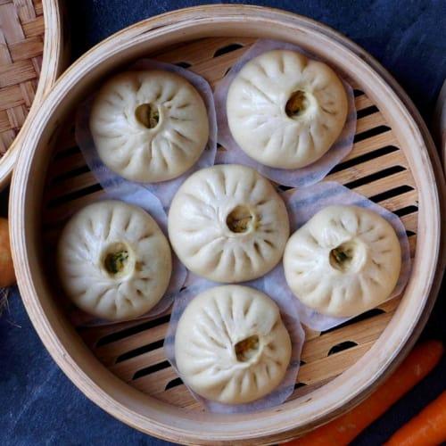 Freshly steamed bao buns in a bamboo steamer.
