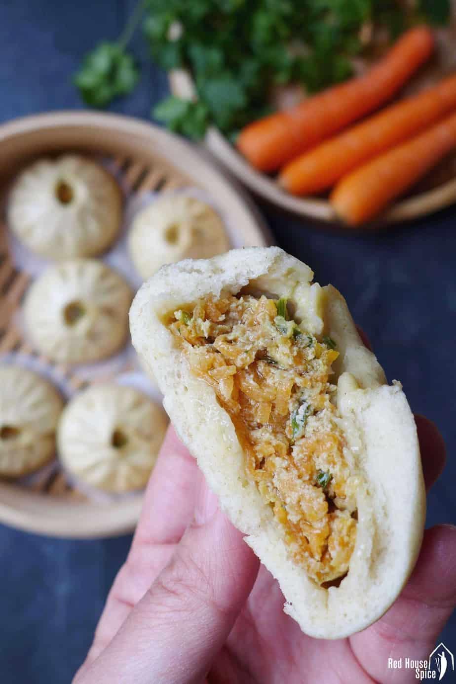 A half eaten steamed bao bun showing the meat & veggie filling.