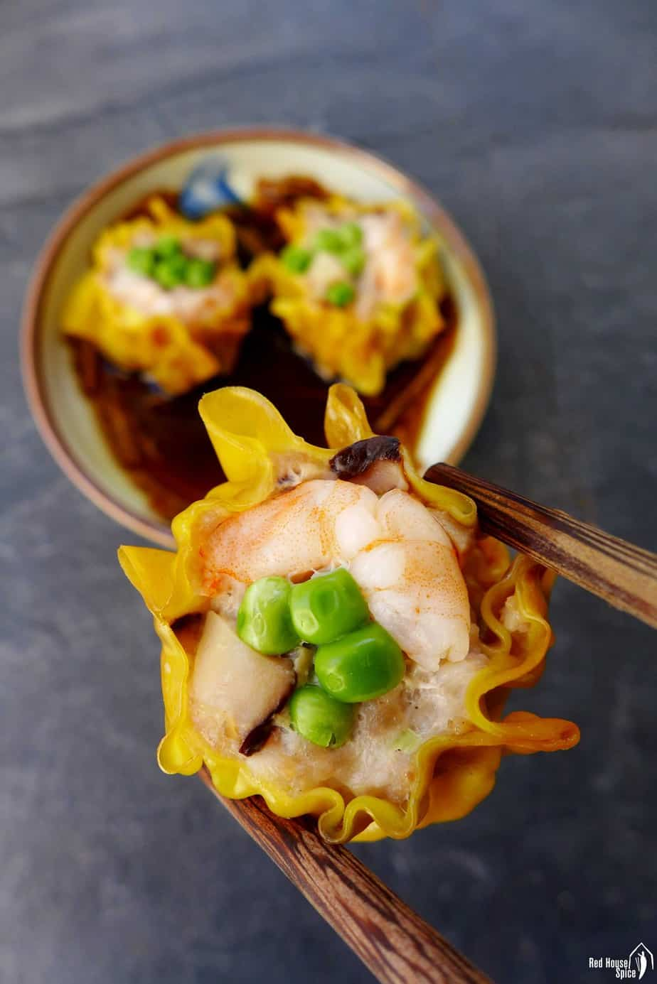 A shrimp & pork shumai held by a pair of chopsticks.