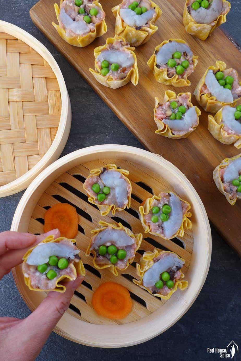Putting freshly made shrimp & pork shumai into a steamer basket.