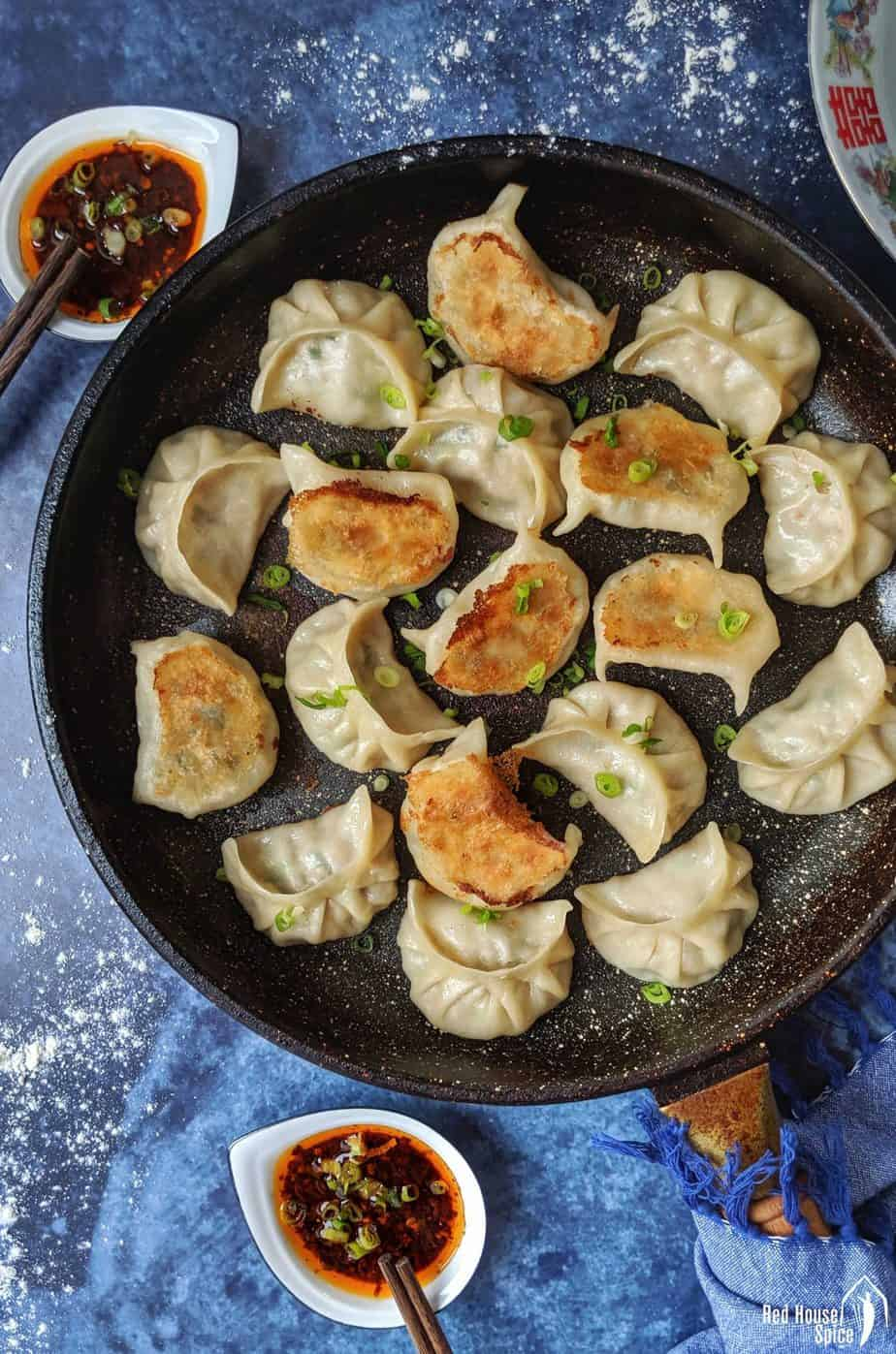Pan fried dumplings with dipping sauce on the side.
