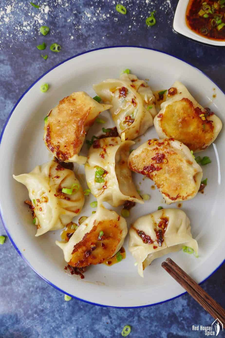 A plate of vegan dumplings covered with spicy sauce