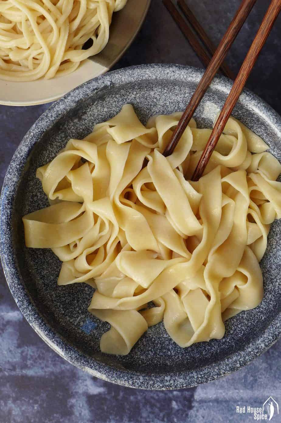 A bowl of plain, wide noodles pulled by hands