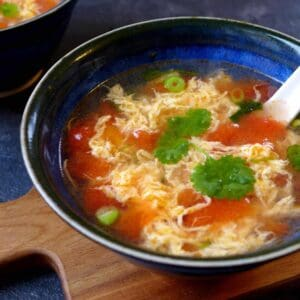 A bowl of egg drop soup with tomato