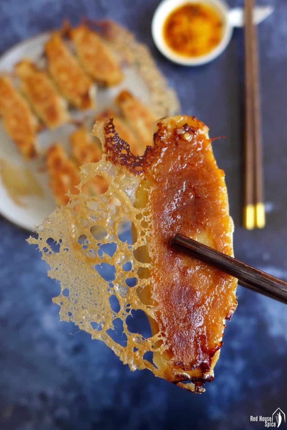 A pan fried dumpling held by a pair of chopsticks