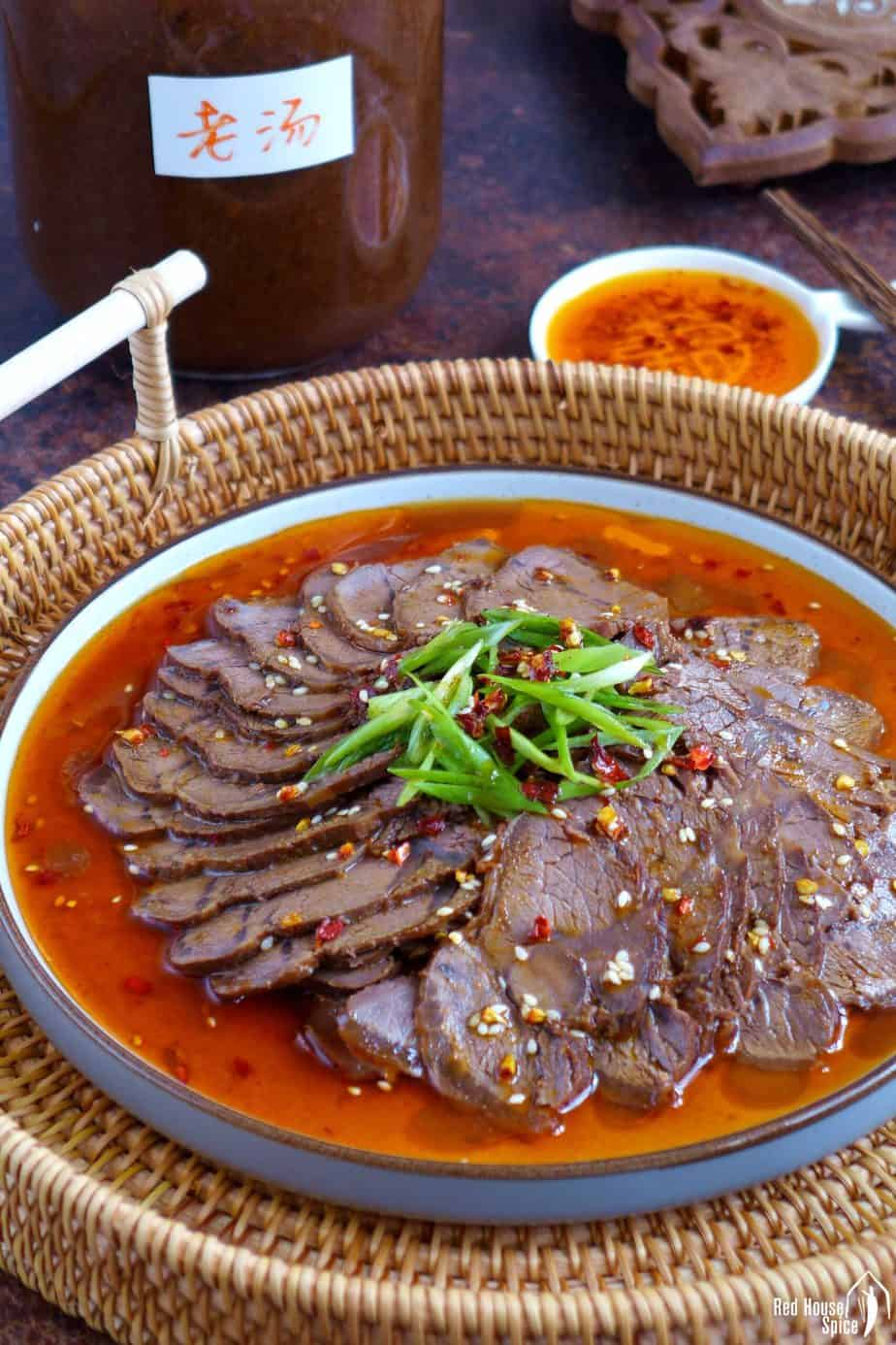 A plate of beef slices and a jar of beef stock