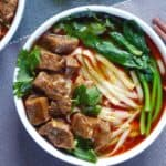 A bowl of noodle soup topped with beef cubes