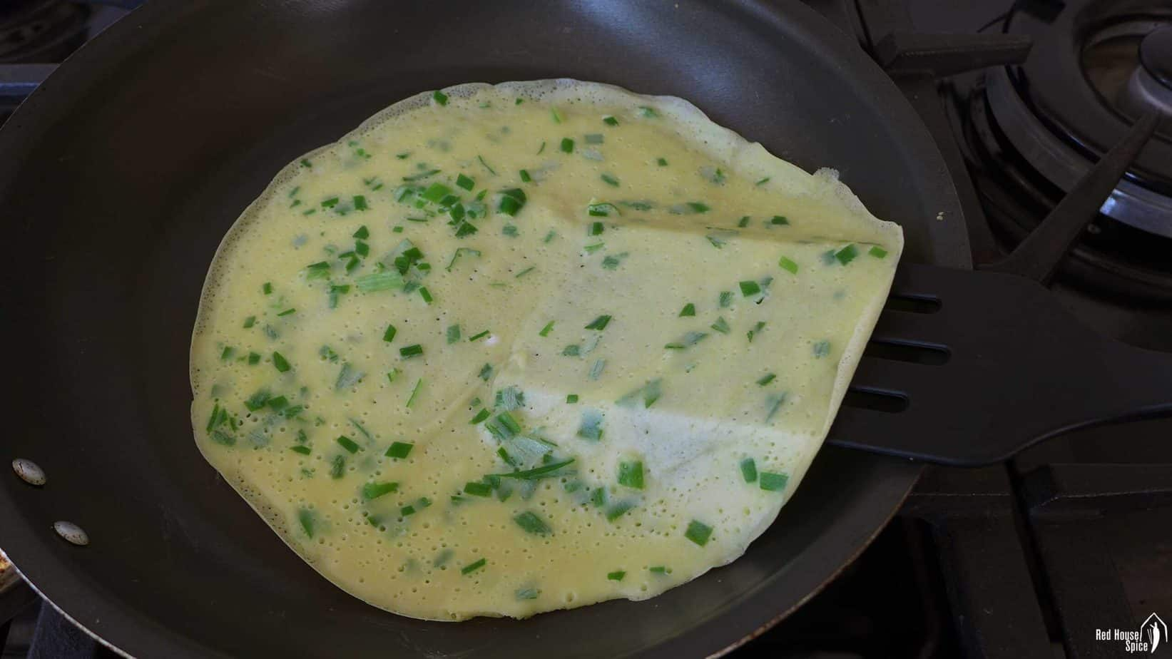 An egg crepe in a frying pan