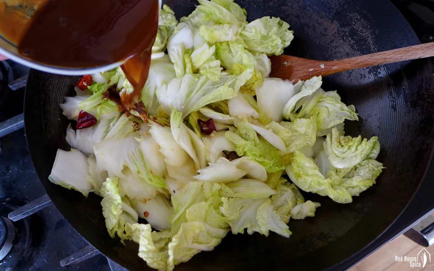 Pouring sauce onto stir-fried napa cabbage