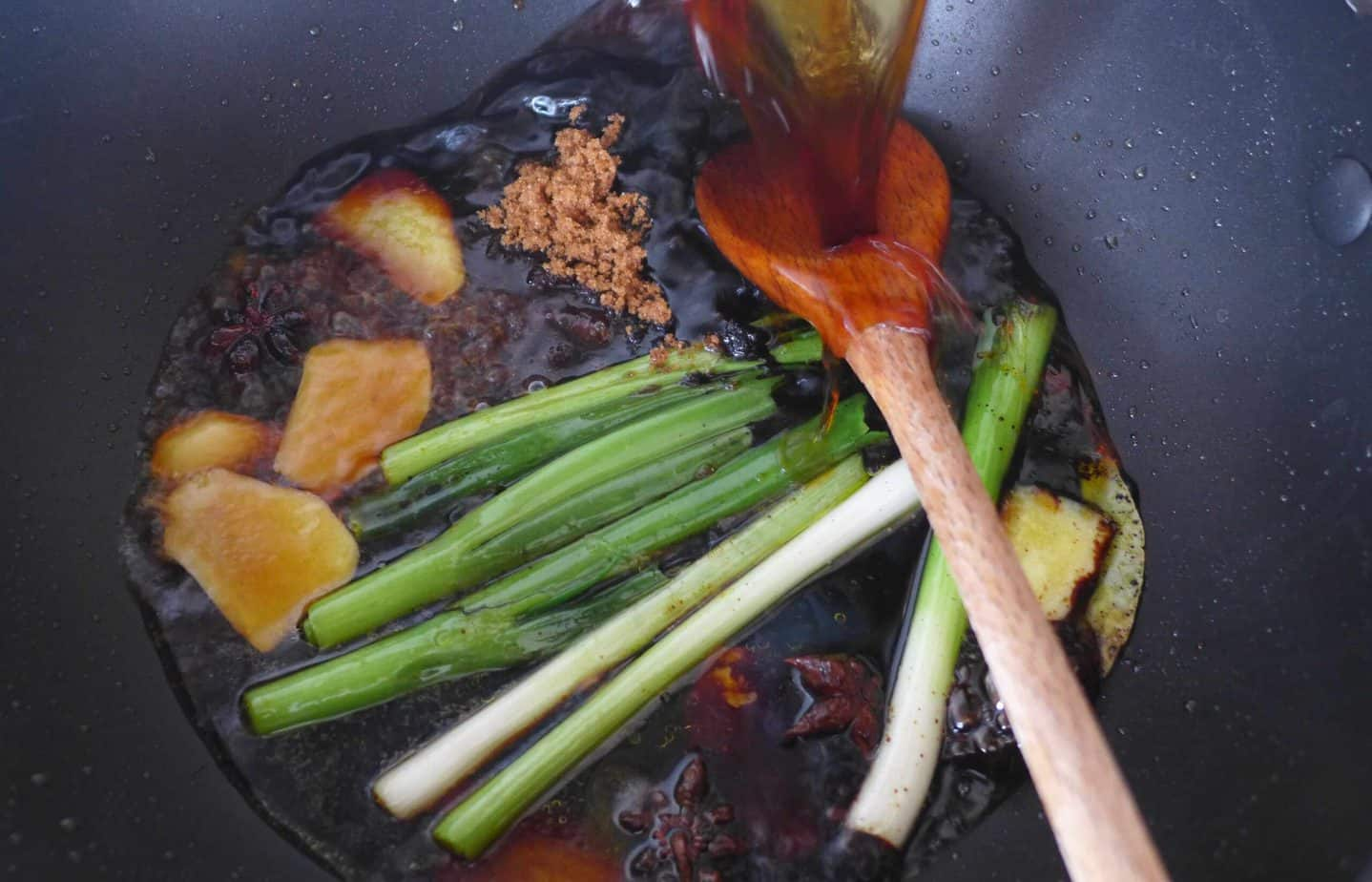 pouring sauce soy into a wok