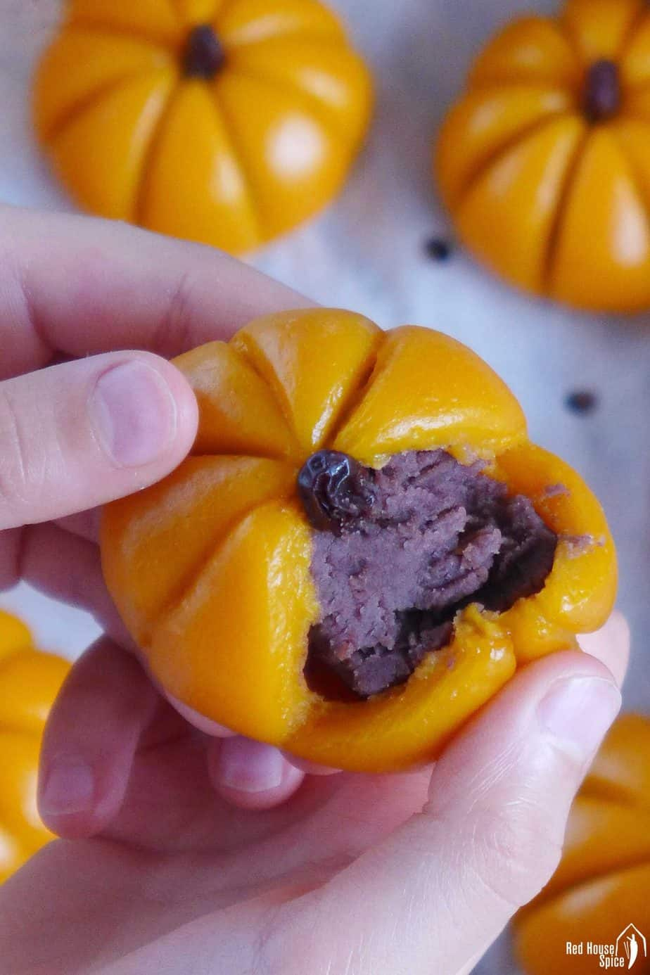 A sticky rice pumpkin cake torn open showing its red bean paste filling.