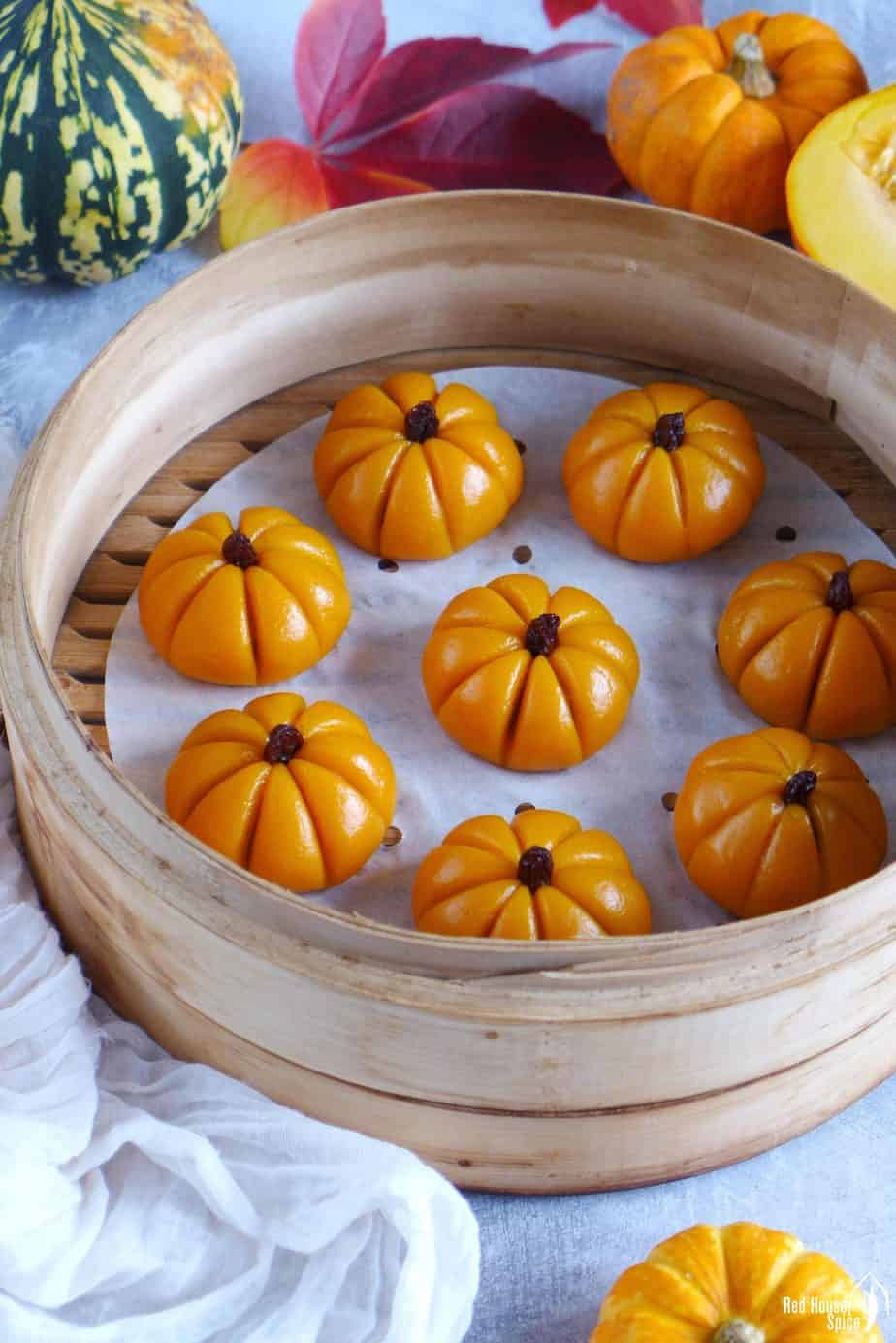 Steamed sticky rice pumpkin cakes in a steamer surrounded by winter squash and leaves.