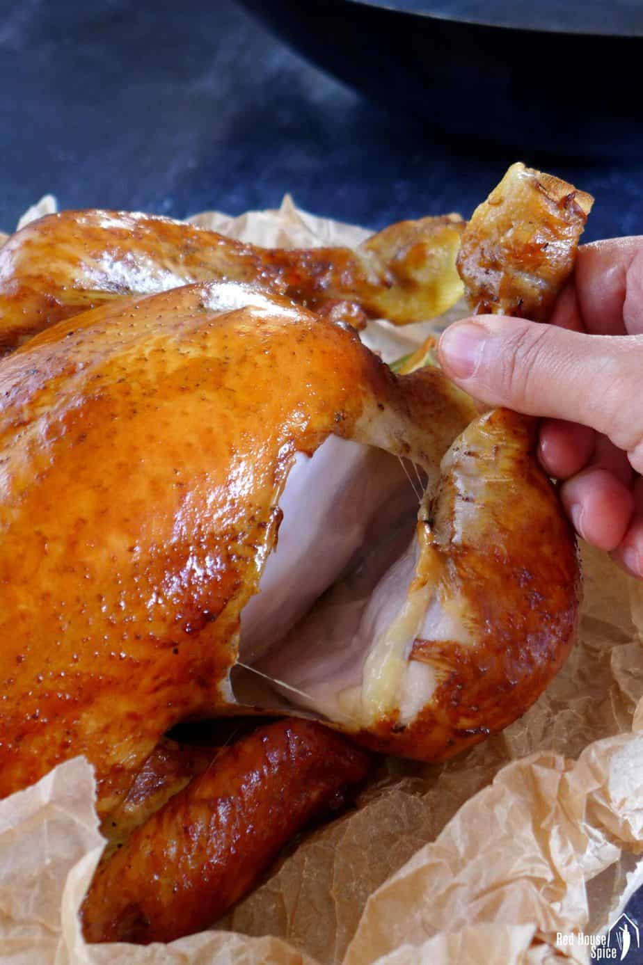 Pulling a leg off a smoked chicken