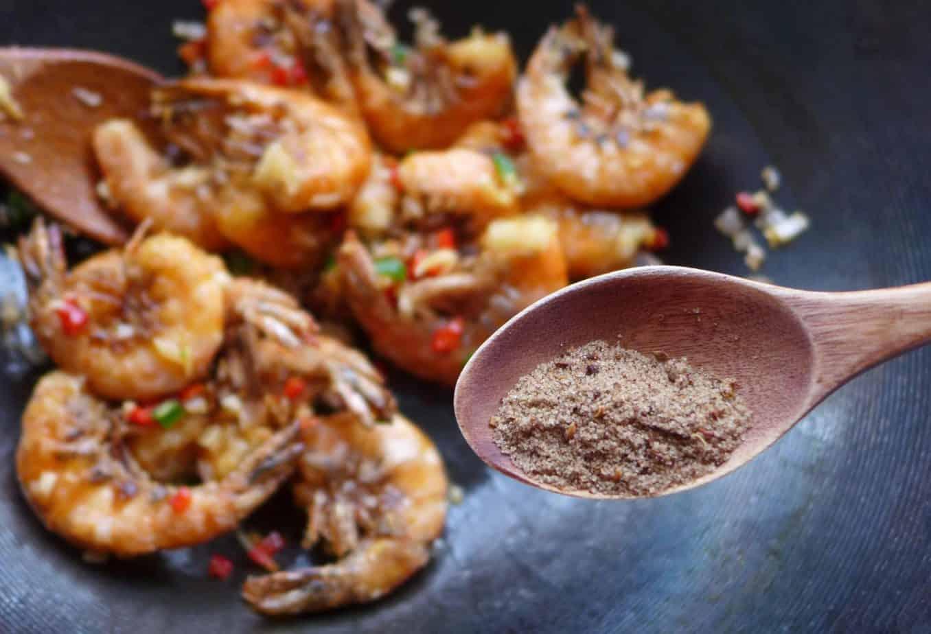 Putting salt and pepper seasoning over shrimp