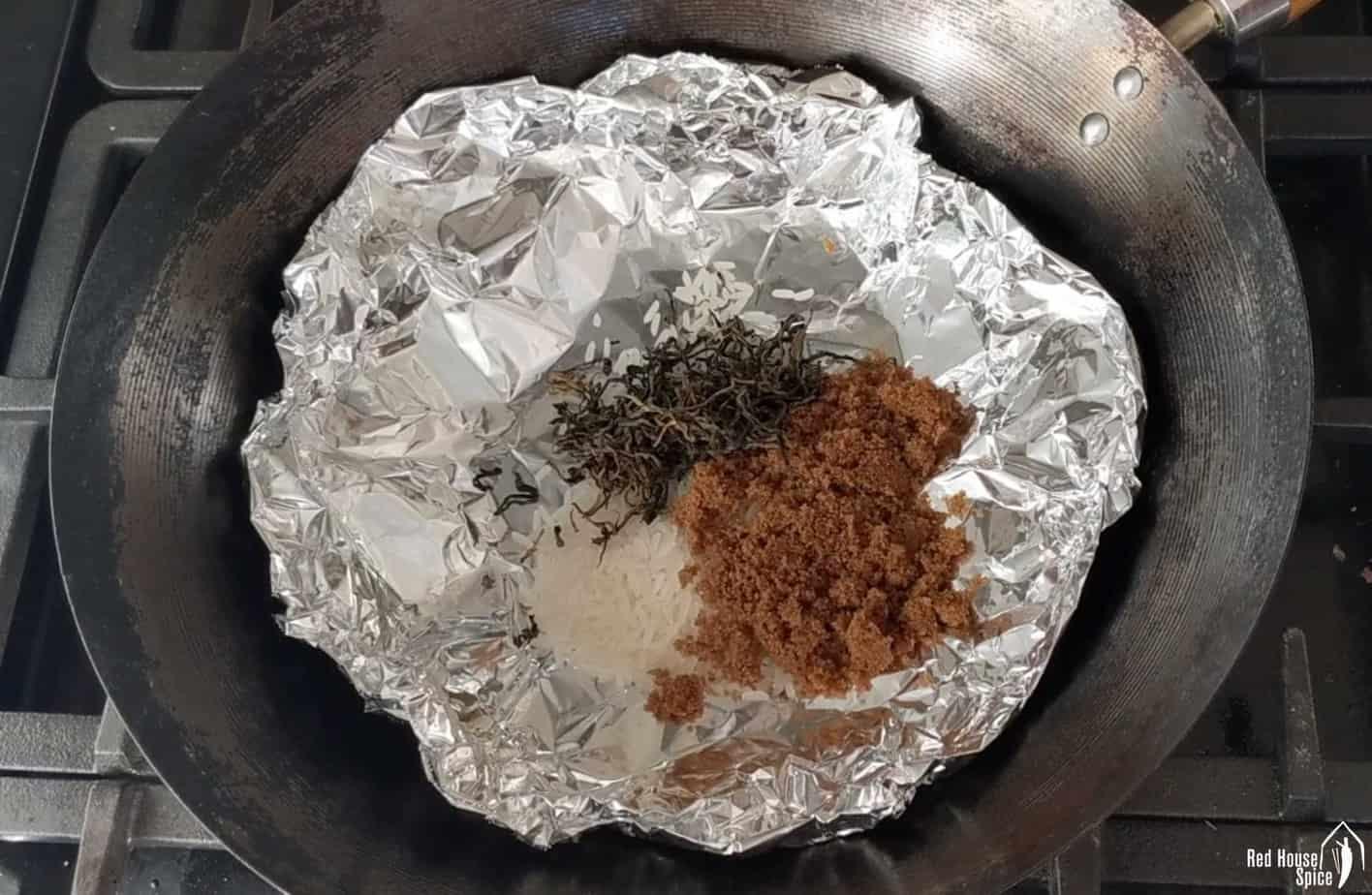 Tea leaves, sugar, rice on kitchen foil inside a wok