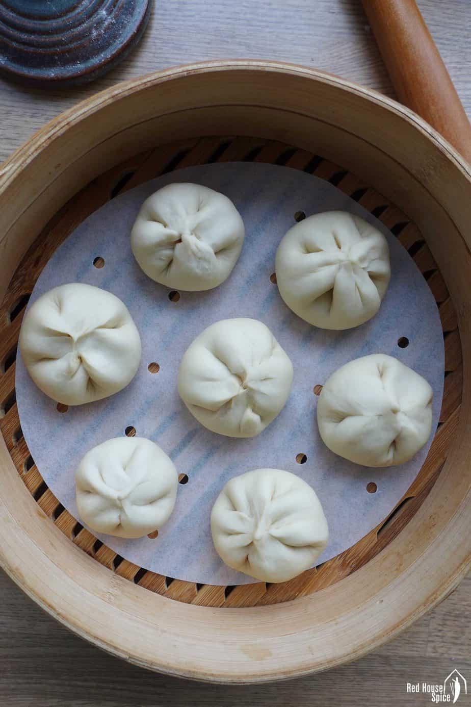 Uncooked Char Siu Bao inside a bamboo steamer
