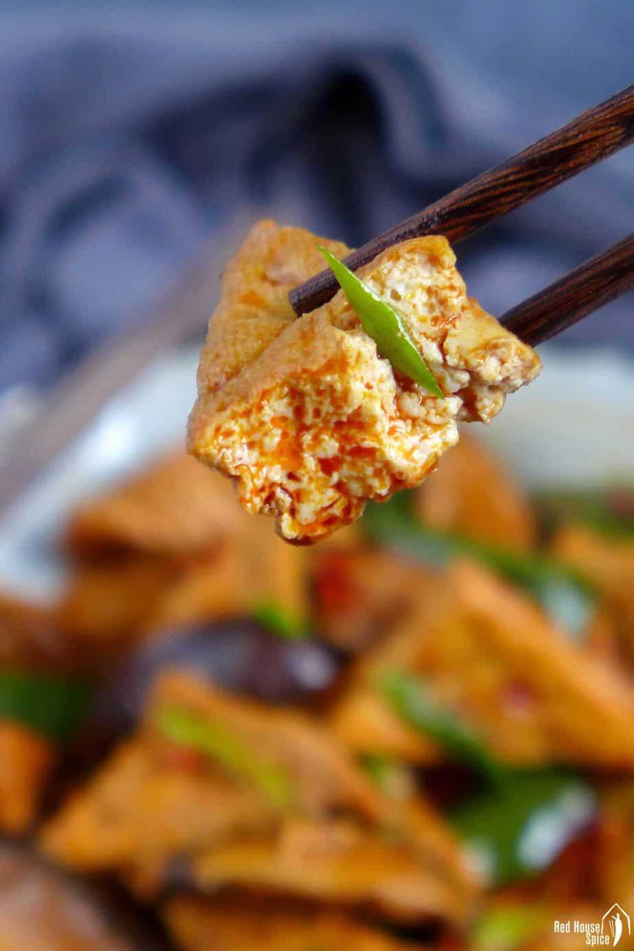 chopsticks picking up a piece of fried tofu