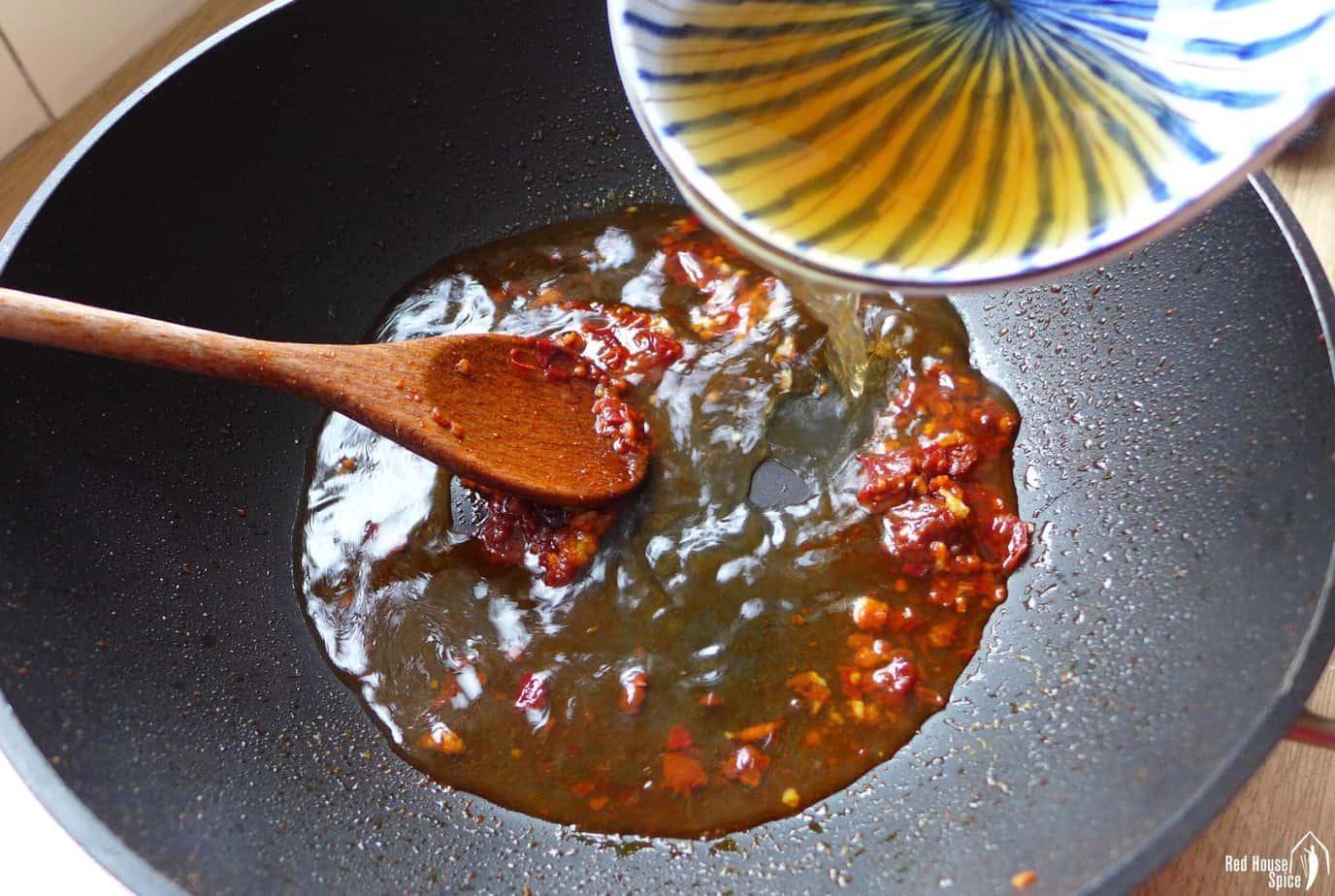 pouring liquid into a wok
