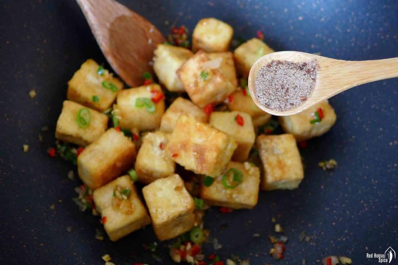 adding salt and pepper seasoning fried tofu