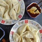 two plates of pork dumplings and a dipping sauce