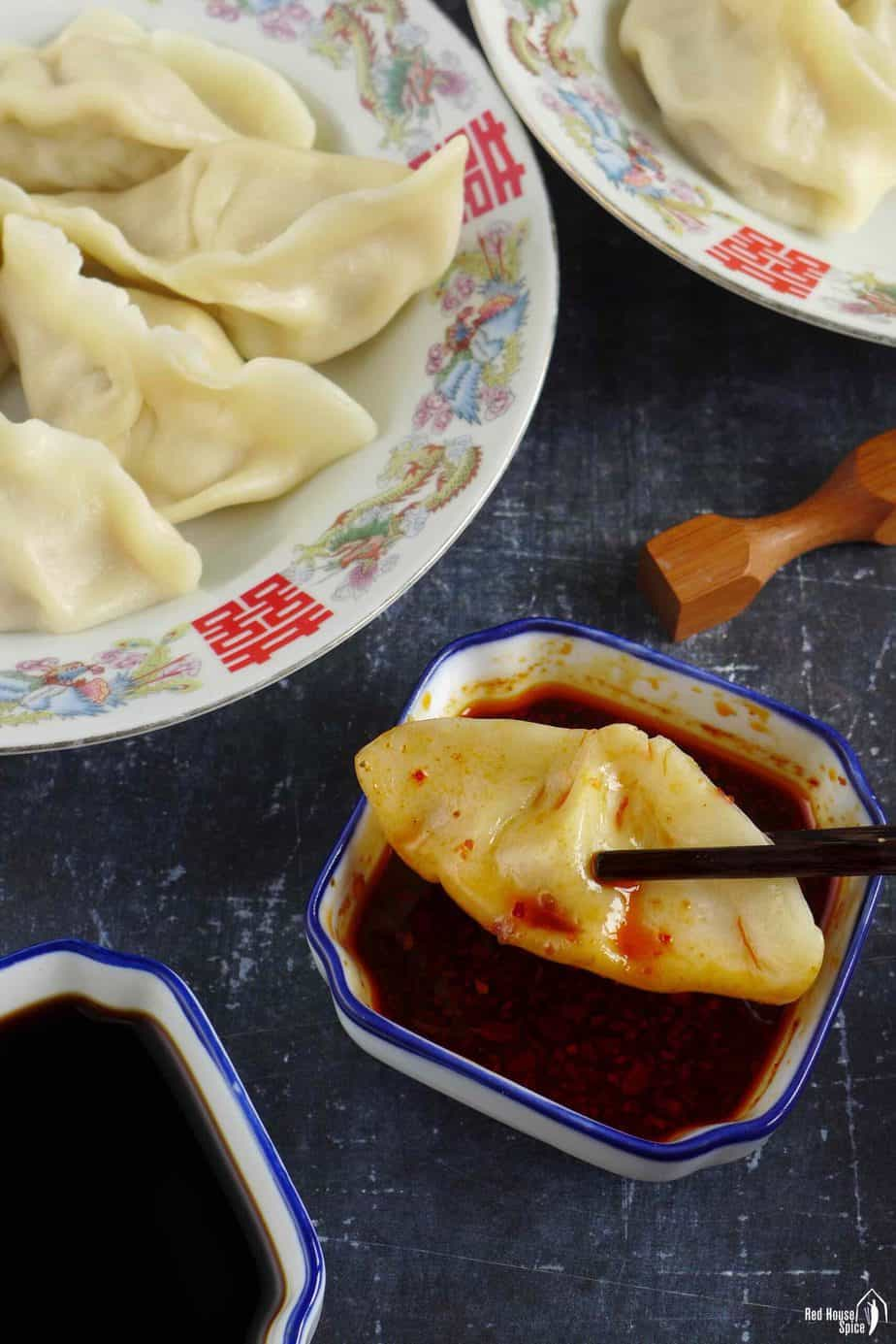 a boiled dumpling in chili dipping sauce