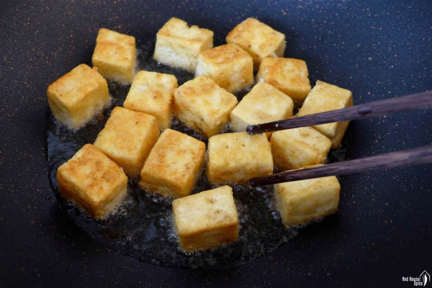 golden coloured tofu cubes in a pan